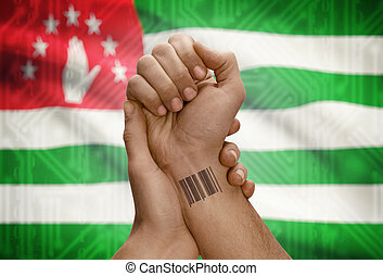 Barcode ID number on wrist of dark skinned person and national flag on background - Abkhazia