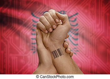 Barcode ID number on wrist of dark skinned person and national flag on background - Albania