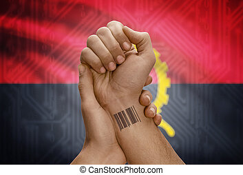 Barcode ID number on wrist of dark skinned person and national flag on background - Angola