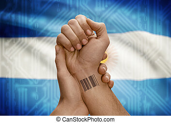 Barcode ID number on wrist of dark skinned person and national flag on background - Argentina