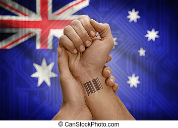 Barcode ID number tattoo on wrist of dark skinned person and national flag on background - Australia