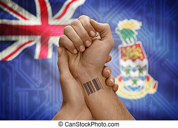 Barcode ID number on wrist of dark skinned person and national flag on background - Cayman Islands