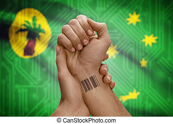 Barcode ID number on wrist of dark skinned person and national flag on background - Cocos (Keeling) Islands