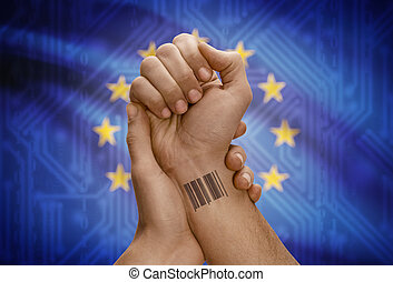 Barcode ID number on wrist of dark skinned person and national flag on background - European Union - EU