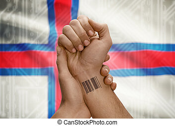 Barcode ID number on wrist of dark skinned person and national flag on background - Faroe Islands