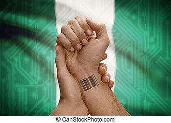 Barcode ID number tattoo on wrist of dark skinned person and national flag on background - Nigeria