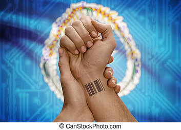 Barcode ID number on wrist of dark skinned person and national flag on background - Northern Mariana Islands