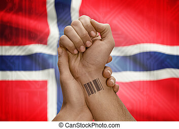 Barcode ID number on wrist of dark skinned person and national flag on background - Norway