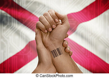 Barcode ID number on wrist of dark skinned person and USA states flags on background - Alabama