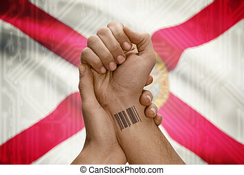 Barcode ID number on wrist of dark skinned person and USA states flags on background - Florida