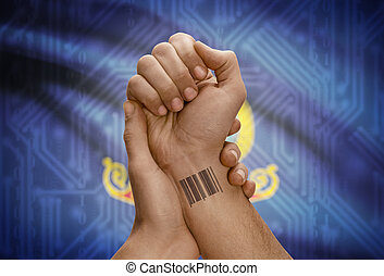 Barcode ID number on wrist of dark skinned person and USA states flags on background - Idaho