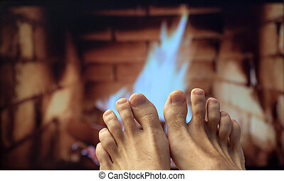 Bare feet are heated by a fireplace