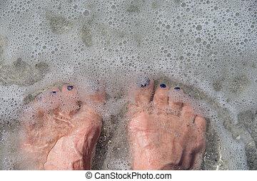 bare feet in ocean water