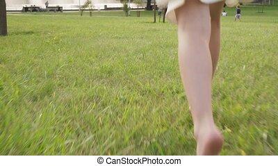 Bare feet of little girl running on grass in summer park,...