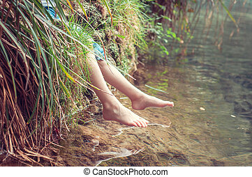 Bare feet of the river. A child enjoying the outdoors. soft focus with vintage processing.