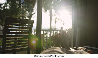 Bare female feet in the bed in early morning in the sun with beautiful lens flare effect.
