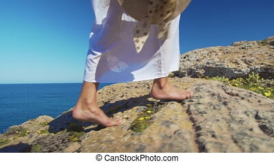 Bare female legs walking feets on rocky terrain