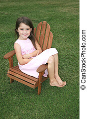 Little girl sitting in a lawn chair