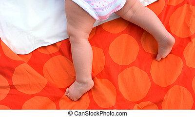 Bare legs of infant baby on blanket.