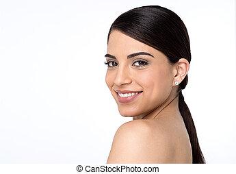 Bare shoulder woman looking into camera