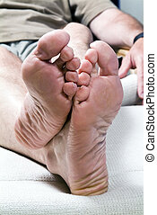 A picture of a man's feet whose tonails are in need of a good pedicure.