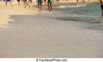 Barefoot beach walking - Tourists walking barefoot on wet...