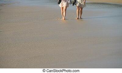 Barefoot beach walking - Women walking barefoot on wet sand...