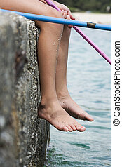 Barefoot child fishing
