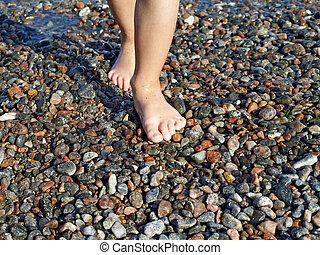 Barefoot child on the wet coastal shingle. Disease prevention feet, flat feet