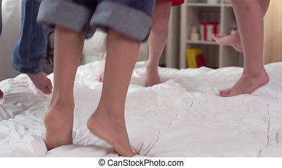 Close-up of barefoot kids jumping on the bed, slow motion