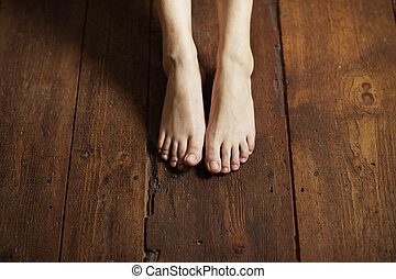 Barefoot - Cropped image of female bare feet on a wooden ...