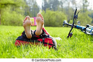 Barefoot cyclist on a halt reads lying in fresh green grass....