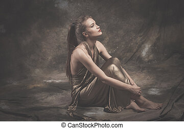 barefoot elegant young woman in golden dress