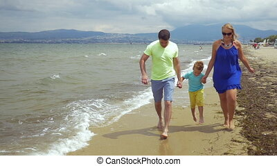 Barefoot family of three running along the sea