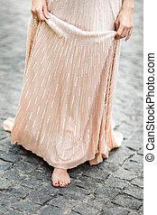 Barefoot feet of bride under wedding dress