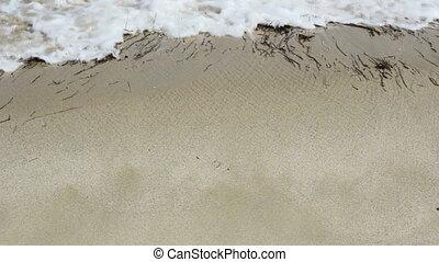 Barefoot feet walking in surf on sand coast. (1920x1080/30p,...