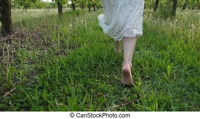 Barefoot female legs running in spring orchard