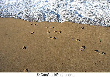 barefoot footsteps on ocean beach sand and wave