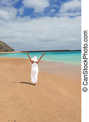 Barefoot girl in white hat and dress standing on a beach