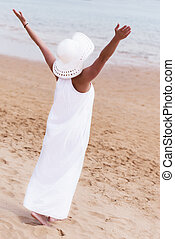 Barefoot girl in white hat and dress standing on a beach with ha
