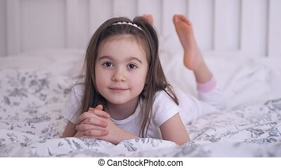 Cute barefoot girl smiling and looking at camera while resting on soft bed at home