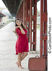 barefoot girl with suitcase waiting at the train station