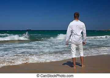 Barefoot guy standing near the sea, horizontal