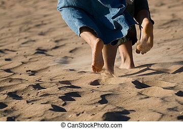 Barefoot legs on the sand beach.