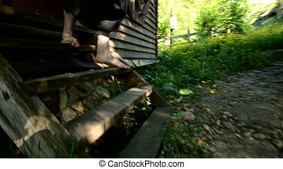 Barefoot man with a stick in black ethnic pants comes out of a rustic wooden house, descends the steps, walks along a rocky road, grass. Summer, sunny day, close-up. Camera is following. Slow motion