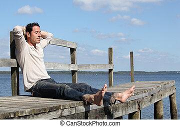 Barefoot man sitting on a wooden jetty enjoying the sunshine