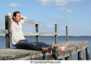 Barefoot man sitting on a wooden jetty enjoying the sunshine