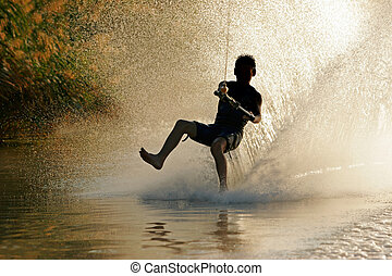 Silhouette of a barefoot skier with backlit water spray Silhouette of a barefoot skier with backlit water spray