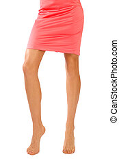 Slim legs of tanned sexy barefoot woman in coral dress on white background