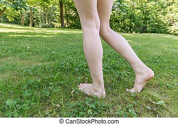 Barefoot walking. Feet of a woman on green grass.